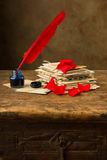 Ink well and red feather quill Royalty Free Stock Photo