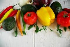Inkasowi świezi warzywa na lekkim tle: pomidory, pieprze, chili, avocado, zielenie, cebula Pojęcie a zdjęcie royalty free