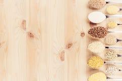 Inkasowi groats w łyżkach na beżowej drewno desce jak dekoracyjną granicę Odgórny widok Zdjęcie Royalty Free