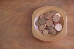 Inkasowych monet pensa miedziani oszczędzania w drewnianym pucharze obrazy stock