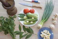 Inkludera den nya organiska grönsaker och gurkan på trägolv Grön gurka, vitlök Sommarram med nya organiska grönsaker Royaltyfri Foto