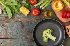 Inkludera den nya organiska grönsaker och stekpannan på trägolv arkivfoto
