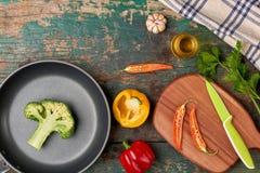 Inkludera den nya organiska grönsaker och stekpannan på trägolv arkivfoton