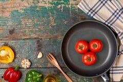 Inkludera den nya organiska grönsaker och stekpannan på trägolv royaltyfri foto