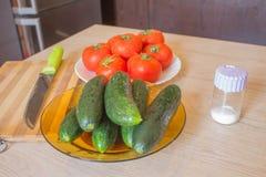 Inkludera nya organiska gr?nsaker p? tr?golv Gurka och tomat på tabellen Gr?nsaker fr?n organisk odlarelantg?rd fotografering för bildbyråer