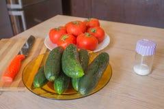 Inkludera nya organiska gr?nsaker p? tr?golv Gurka och tomat p? tabellbakgrund rganic odlarelantg?rd arkivbilder