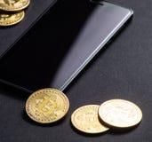 Inkomens op crypto-munten: gouden muntstukken bitcoin en smartphone op een donkere achtergrond Vierkant frame royalty-vrije stock foto