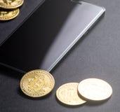 Inkomens op crypto-munten: gouden muntstukken bitcoin en smartphone op een donkere achtergrond Vierkant frame stock fotografie