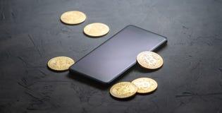Inkomens op crypto-munten: gouden muntstukken bitcoin en smartphone op een grijze achtergrond Horizontaal kader royalty-vrije stock foto's