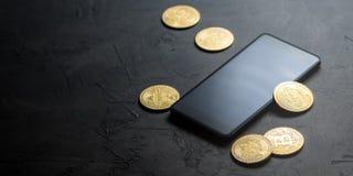 Inkomens op crypto-munten: gouden muntstukken bitcoin en smartphone op een grijze achtergrond Horizontaal kader stock foto