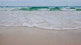 Inkommande våg på den silkeslena sandstranden Arkivfoto