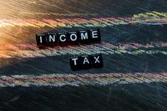 Inkomstenbelasting op houten blokken Kruis verwerkt beeld met bordachtergrond stock foto's