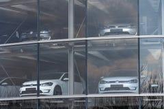 Inkopplingshybrid- Volkswagen e-golf elbilar står bak exponeringsglas i Glasernen Manufaktur - den genomskinliga fabriken, Dresde Arkivfoton