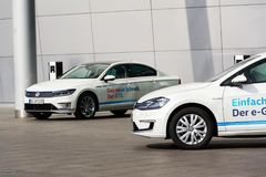 Inkopplingshybrid- Volkswagen Golf GTE- och e-golf elbilar står vid uppladdningsstationen framme av Glasernen Manufaktur Arkivbilder