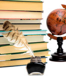 Inkstand, pen, books and a globe on a white background Royalty Free Stock Photo