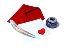 Inkstand with a quill near envelope and red heart Stock Image