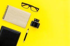Inkt, onderdompelingspen, notitieboekje, glazen voor schrijverswerkplaats op geel bureau achtergrond hoogste meningsmodel dat wor Stock Foto's