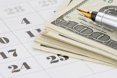 Inkt pen en dollargeld op kalender Stock Afbeelding