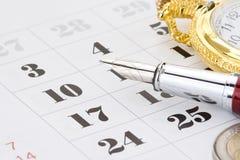 Inkt pen en muntstukgeld op kalender Royalty-vrije Stock Foto's