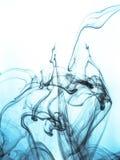 Inktwerveling in een water op kleurenachtergrond De verfplons in het water Zachte verspreiding druppeltjes van gekleurde inkt bin Stock Afbeelding