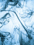 Inktwerveling in een water op kleurenachtergrond De verfplons in het water Zachte verspreiding druppeltjes van gekleurde inkt bin Royalty-vrije Stock Afbeelding