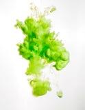 Inktwerveling in water op witte achtergrond wordt geïsoleerd die De verf in het water Zachte verspreiding druppeltjes van groene  royalty-vrije stock foto's