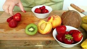 Inkvartera i det civila för fruktcoctail på bananer för en skärbräda, jordgubbar, persika En kvinna sätter jordgubbarna i en bunk lager videofilmer