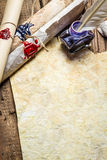 Inkwell and ancient scrolls on old sheet of paper. On old wooden table Royalty Free Stock Image