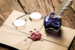 Inkwell with feather on envelope with red sealant and glasses Royalty Free Stock Photo