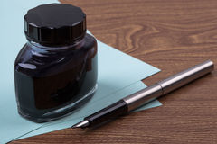 Inkwell and fountain pen on wooden texture Stock Photo