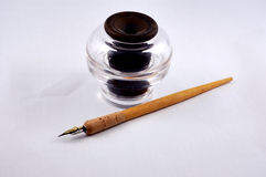 Inkwell and Pen. An antique glass inkwell and wooden pen and nib Royalty Free Stock Photography