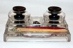 Inkwells and Pens. An antique glass inkstand with two old wooden pens and a bunch of nibs Royalty Free Stock Photos