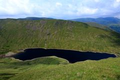 Inky blue waters of a Lake District mountain tarn. Fresh water lake in a spectacular mountain setting in the English Lake District National Park on a summer day Royalty Free Stock Photos