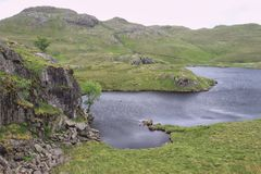 Inky blue waters of a Lake District mountain tarn. Fresh water lake in a spectacular mountain setting in the English Lake District National Park on a summer day Royalty Free Stock Image