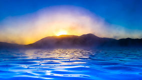 Inky Seascape. Color enhanced scene of a blue inky sea with a dark mountainous skyline silhouetted against an orange setting sun. A thick mist rises from the Royalty Free Stock Photo
