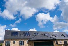 Inländische Sonnenkollektoren auf der Dachspitze von eben gebauten Häusern Stockfoto