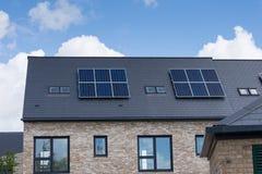 Inländische Sonnenkollektoren auf der Dachspitze von eben gebauten Häusern Stockfotos