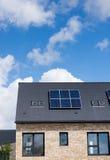 Inländische Sonnenkollektoren auf der Dachspitze von eben gebauten Häusern Stockbild