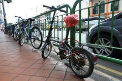 Inlåst cykel staketet av Singapore royaltyfri foto