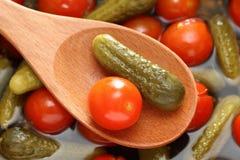 Inlagd tomat och gurka i en träsked Arkivbilder