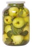Inlagda äpplen i en glass krus Arkivbild