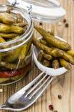Inlagda Chilis i ett exponeringsglas Arkivbild