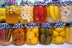 Inlagda grönsaker och frukt i krus Royaltyfri Bild