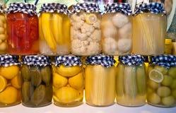 Inlagda grönsaker och frukt i krus Royaltyfri Foto