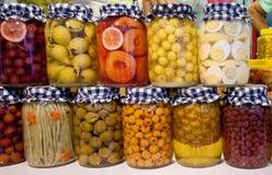 Inlagda grönsaker och frukt i krus Royaltyfria Foton