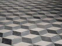 Inlaid geometric patterned stone or marble floor. With a repeat motif of tiles giving a perception of a three dimensional design Stock Photography