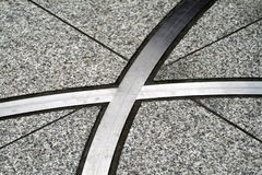 Inlaid steel markings. A view of strips of steel or aluminum where they intersect as part of a pattern inlaid in marble or concrete flooring Royalty Free Stock Photos