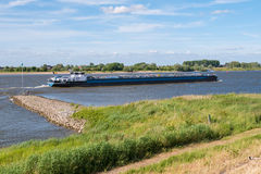 Inland tanker sailing upstream on river Waal, Netherlands. Inland tank ship sailing upstream on river Waal and fishing man on groyne on south bank near Zuilichem Stock Photo