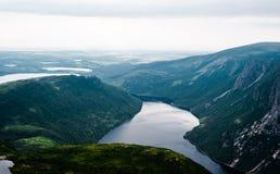 Inlands- fjord mellan branta klippor mot grönt landskap Royaltyfria Bilder