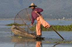 Inle Lake Fisherman. Young fisherman with his wooden boat on Lake Inle, Central Myanmar (former Burma Royalty Free Stock Image